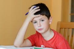 Trött och uttråkad pojke som gör skolaläxa arkivbild