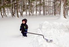 Trött pojke som försöker att skyffla snö Arkivbild