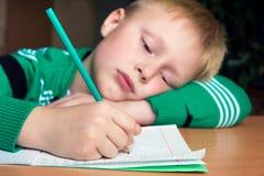 Trött pojke som gör svår läxa arkivfoton