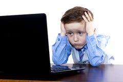 Trött pojke med bärbar dator Fotografering för Bildbyråer