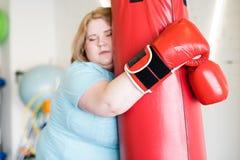 Trött sjukligt fet kvinnautbildning i idrottshall arkivbild
