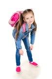 Trött skolflicka med den isolerade tunga ryggsäcken Fotografering för Bildbyråer
