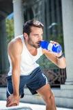 Trött stiligt idrotts- dricka ut ur flaskan royaltyfria foton