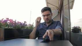 Trött stiligt mansammanträde i kafé med telefonen stock video