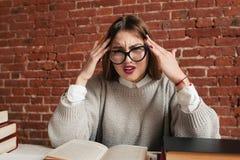 Trött stressat studentsammanträde på skrivbordet med böcker Arkivfoto