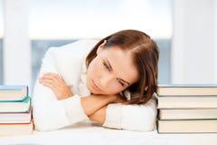 Trött student med böcker och anmärkningar royaltyfri fotografi