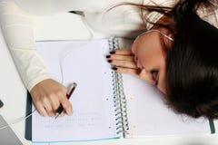 Trött student som är stupad sovande på tabellen Arkivfoton