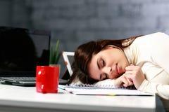 Trött student som är stupad sovande på tabellen Royaltyfria Bilder