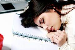 Trött student som är stupad sovande på tabellen Arkivfoto