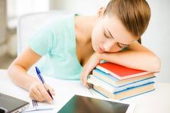 Trött student som sover på materiel av böcker Fotografering för Bildbyråer