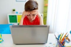 Trött studentpojke med bärbar datordatoren hemma Arkivfoton