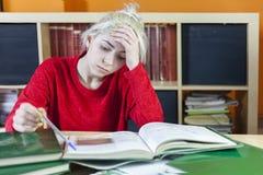 Trött studentsammanträde med många bokar, med hennes huvud i hand royaltyfria foton