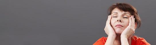 Trött 50-talkvinna som kopplar av för att undvika varma exponeringar, grått baner Arkivfoto