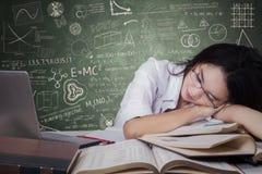 Trött tonårs- student som sover på skrivbordet royaltyfri fotografi