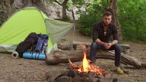 Trött turist- sammanträde nära lägerelden, i att campa stock video