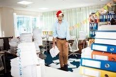 Trött ung affärsman som i regeringsställning arbetar bland legitimationshandlingar på juldag Royaltyfri Fotografi