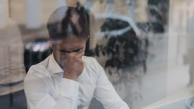 Trött ung affärsman som sitter på en tabell i ett kaféarbete på en bärbar dator Frilans kommunikation, DET som är trött lager videofilmer