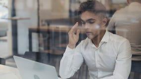 Trött ung affärsman som sitter på en tabell i ett kaféarbete på en bärbar dator Frilans kommunikation, DET som är trött arkivfilmer