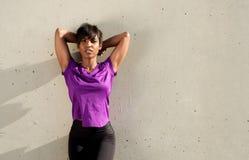 Trött ung afrikansk kvinna som utomhus kopplar av till en vägg efter genomkörare Arkivbild
