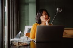 Trött ung asiatisk kvinna i hennes kontor royaltyfria bilder