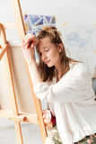 Trött ung caucasian dammålare på workspace Royaltyfria Bilder