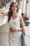Trött ung flicka i den vita klänningen och med den blåa påsen royaltyfria foton