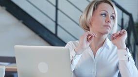 Trött ung kvinna i kontoret som arbetar med en bärbar dator och stirrar på datorskärmen arkivfilmer