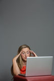 Trött ung kvinna som arbetar på en bärbar dator Arkivbilder