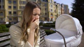 Trött ung kvinnlig som inte försöker att falla ta sovande omsorg av nyfött i vagn stock video