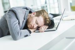 Trött ung man som sover i kontoret Arkivbild