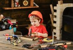 Trött unge som spelar i seminarium Litet bulta för pojke spikar Litet barn i den orange hjälmen som sitiing på det funktionsdugli arkivbild