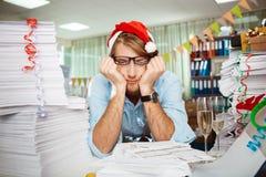 Trött ungt affärsmansammanträde på arbetsplatsen bland legitimationshandlingar på juldag Arkivbilder