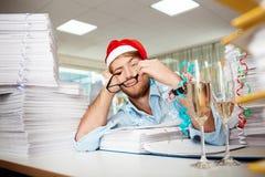 Trött ungt affärsmansammanträde på arbetsplatsen bland legitimationshandlingar på juldag Royaltyfri Bild