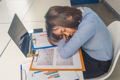 Trött ungt asiatiskt ta för affärskvinna ta sig en tupplur i affärsmötesrummet royaltyfri foto