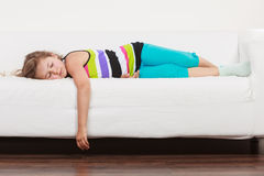 Trött utmattad lat liten flickaunge som ligger på soffan Arkivfoto