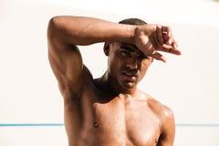 Trött våt idrotts- afrikansk manavtorking svettas med hans hand royaltyfria foton