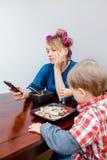 Trött vit Caucasian moderhemmafru för ung kvinna med papiljotter i hår som ser på telefonen som surfar internet Royaltyfri Foto