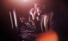 Trötta anställda som arbetar i kontoret på natten arkivfoto