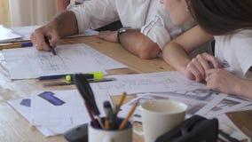 Trötta kontorsarbetare diskuterar om teckningar, arkitektoniska teckningar stock video