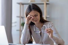 Trötta kvinnagnuggbildögon som känner trötthet från exponeringsglasdatorarbete arkivbild