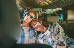 Trötta kvinnavänner som sover i en bil för bakre plats Royaltyfri Foto