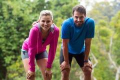 Trötta par som tar ett avbrott, medan jogga Fotografering för Bildbyråer