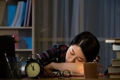 Trötta studenter som studerar att sova på skrivbordet royaltyfri bild