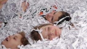 Trötta ungar som ligger i papper som har after ett stort parti stock video