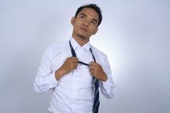 Tröttad asiatisk affärsman, medan ta bort bandet Royaltyfria Foton