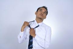 Tröttad asiatisk affärsman, medan ta bort bandet Arkivfoto