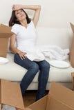 Tröttad enkel kvinna packa upp askar som flyttar huset Arkivfoto