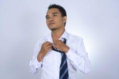 Tröttad fotobild av den asiatiska affärsmannen, medan ta bort skjortaknappar Royaltyfria Bilder
