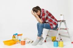 Tröttad kvinna i tillfällig kläder som sitter på stege med instrument för renoveringlägenhetrum som isoleras på vit arkivfoton