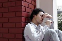 Tröttad stressad ung asiatisk känsla för affärsman som svikas eller evakueras med jobb på det utvändiga kontoret arkivfoton